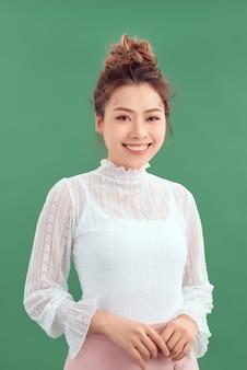 緑の背景の上にカメラで探している若いアジアの女性の肖像画。