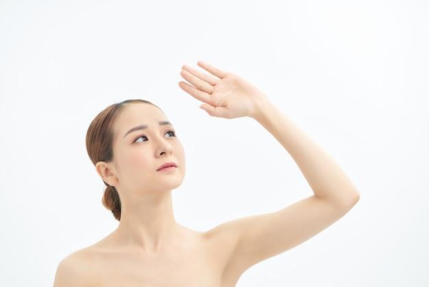 横を見て、白い背景に手を示す若いアジアの女性の肖像画。