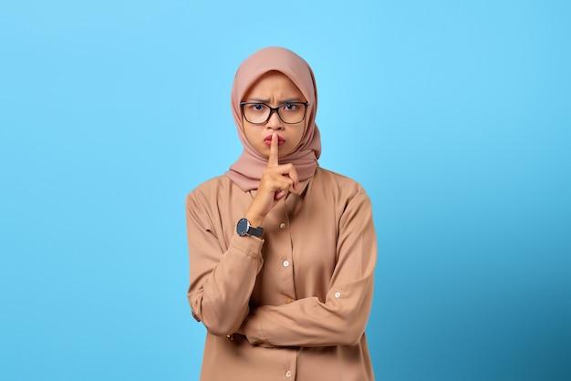 若いアジアの女性の肖像画は指の手で沈黙のジェスチャーをします