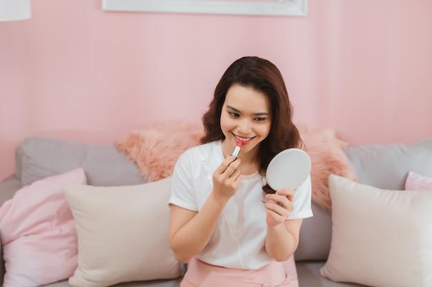 비디오를 녹화하는 젊은 아시아 여자의 초상화 집에서 립스틱 화장품을 구성합니다. 온라인 인플 루 언서 소녀 소셜 미디어 마케팅 라이브 김이 나는 개념