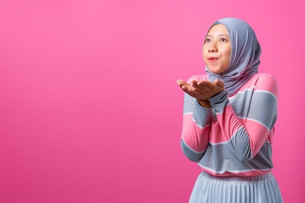 若いアジアの女性の肖像画はピンクの背景にエアキスを送信します