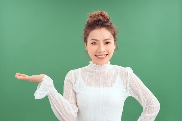 製品を示すために彼女の手を示す若いアジアの女性の肖像画。緑の背景の上に分離されました。