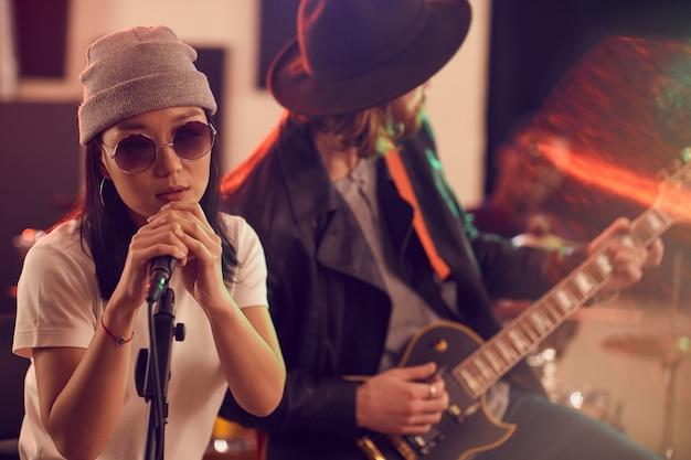 Портрет молодой азиатской женщины поет в микрофон во время музыкального концерта
