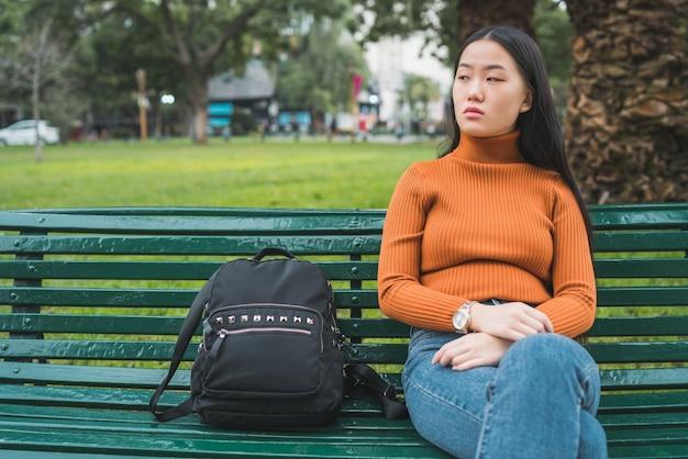 Портрет молодой азиатской женщины, сидящей на скамейке в парке на открытом воздухе.
