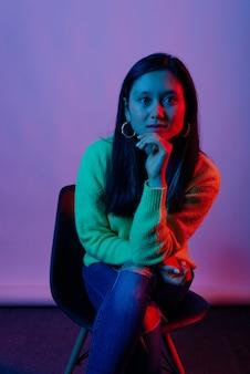 Портрет молодой азиатской женщины сидя на стуле и смотря уверенно