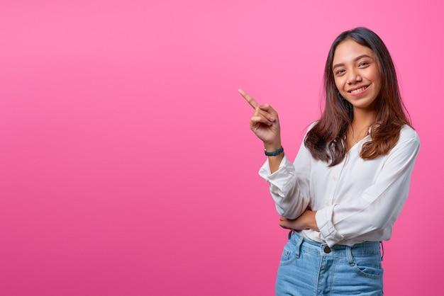 笑顔と空のスペースを指している若いアジアの女性の肖像画