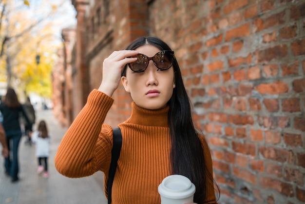 Портрет молодой азиатской женщины, стоящей на улице.