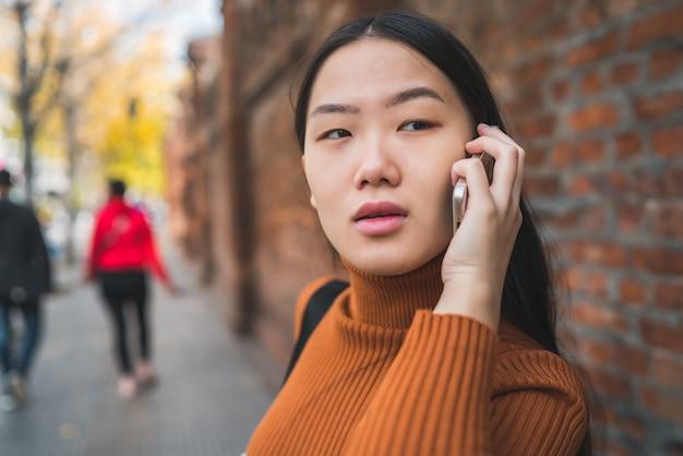 通りで屋外の電話で話している若いアジア女性の肖像画。都市とコミュニケーションの概念。