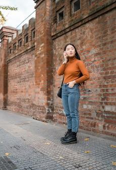 通りの屋外で電話で話している若いアジアの女性の肖像画。都市とコミュニケーションの概念。