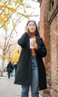 通りでコーヒーを飲みながら電話で話している若いアジアの女性の肖像画。都市とコミュニケーションの概念。