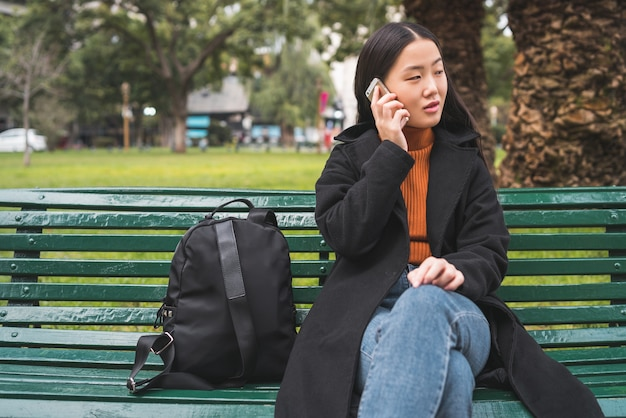 公園のベンチに座っている間電話で話している若いアジア女性の肖像画。コミュニケーションの概念。