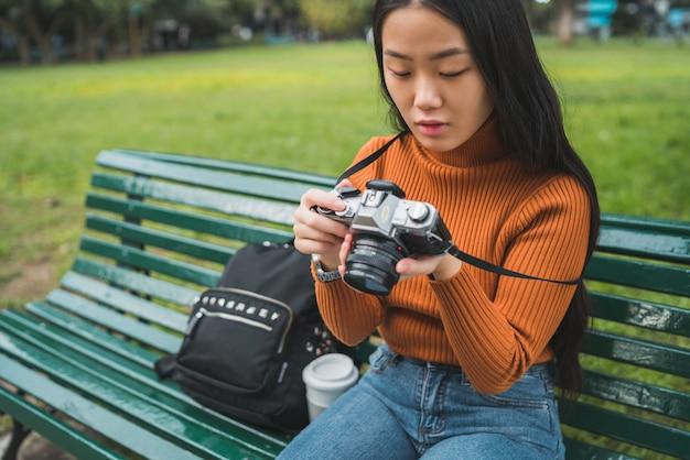 Портрет молодой азиатской женщины, использующей профессиональный цифровой фотоаппарат в парке на открытом воздухе. концепция фотографии.