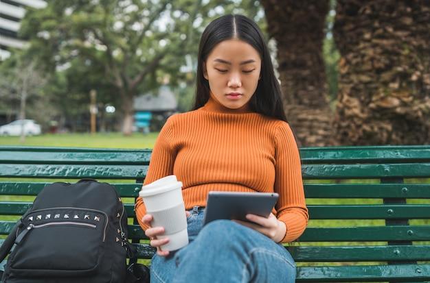 Портрет молодой азиатской женщины, использующей ее цифровой планшет, держа чашку кофе в парке на открытом воздухе.
