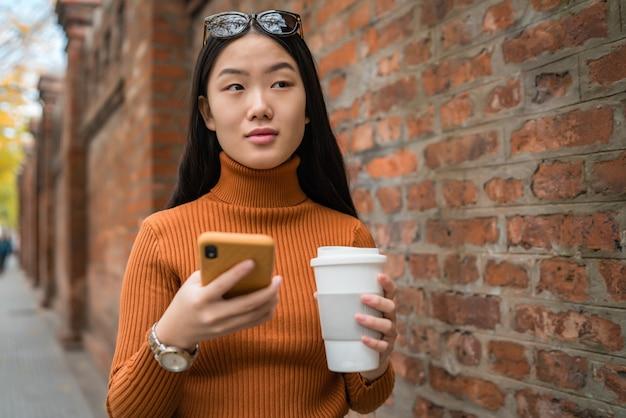 通りで彼女の携帯電話を使用して若いアジアの女性の肖像画。都市とコミュニケーションの概念。