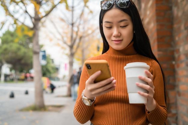 通りで彼女の携帯電話を使用して若いアジアの女性の肖像画。