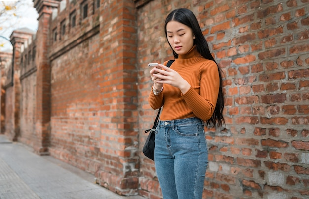 通りで屋外に彼女の携帯電話を使用して若いアジアの女性の肖像画。都市とコミュニケーションの概念。