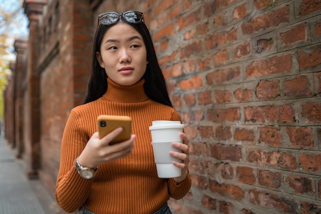 通りで一杯のコーヒーを押しながら彼女の携帯電話を使用して若いアジアの女性の肖像画。都市とコミュニケーションの概念。