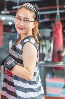 ジムでボクシングを練習しているボクシンググローブを着ている若いアジアの女性の肖像画。 Premium写真