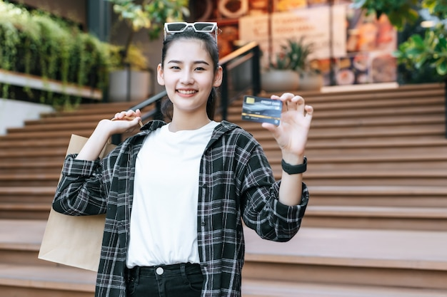 쇼핑 종이 가방과 함께 계단에 서 안경을 쓰고 젊은 아시아 여자의 초상화