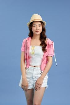 파란색 배경에 격리된 모자, 티셔츠, 짧은 청바지, 분홍색 재킷을 입은 젊은 아시아 여성의 초상화.