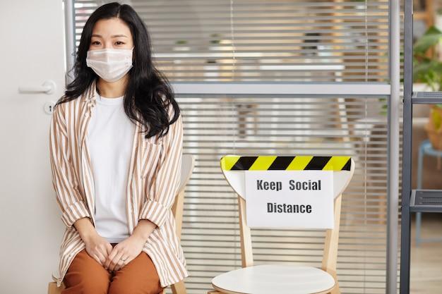 마스크를 착용하고 사회 거리 유지 기호로 사무실에서 줄을 서서 기다리는 동안 카메라를보고 젊은 아시아 여자의 초상화, 복사 공간