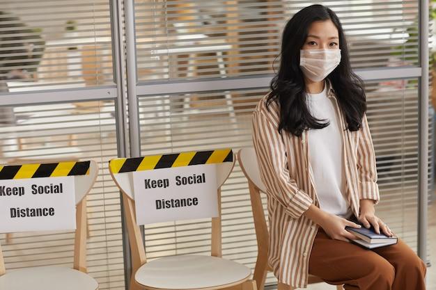 마스크를 착용하고 사회적 거리 유지 표지판과 함께 기다리는 동안 카메라를보고 젊은 아시아 여자의 초상화, 복사 공간
