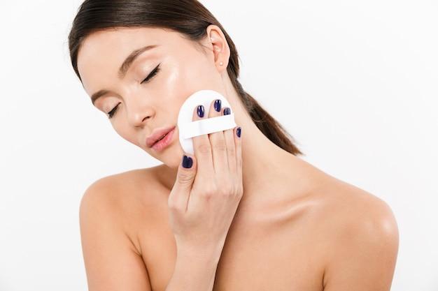 白で分離された化粧品のスポンジで顔にコンシーラーまたはパウダーを適用するきれいな健康な皮膚を持つ若いアジア女性の肖像画