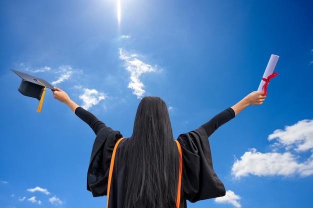 屋外で卒業証書を持つ若いアジア女性のポートレート