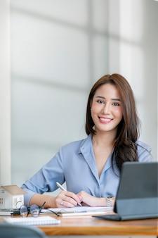 Портрет молодой азиатской женщины работая на ее офисном столе, усмехаясь и смотря камеру. вертикальный вид.