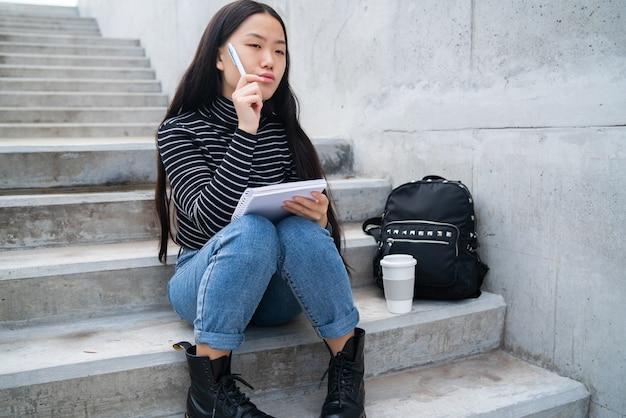 Портрет молодой азиатской женщины, писать на тетради, сидя на открытом воздухе на бетонной лестнице.