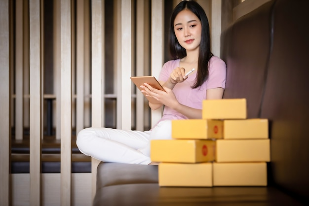 ラップトップコンピューターを自宅でオンラインショッピング若いアジアの肖像画。オンライン販売と配信のコンセプト