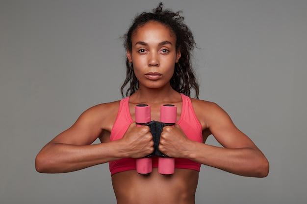 Портрет молодой спортивной кареглазой темнокожей женщины с непринужденной прической, держащей утяжелители на уровне груди и спокойно смотрящей со сложенными губами, изолированной