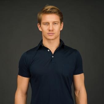 회색 공간에 서있는 동안 진한 파란색 폴로 티셔츠를 입고 젊은 운동 남자의 초상화