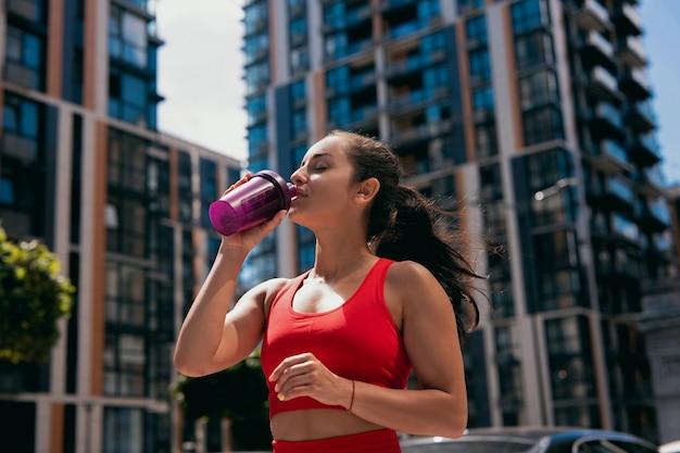 Портрет молодой спортивной женщины в красном бюстгальтере питьевой воды из спортивной бутылки после бега