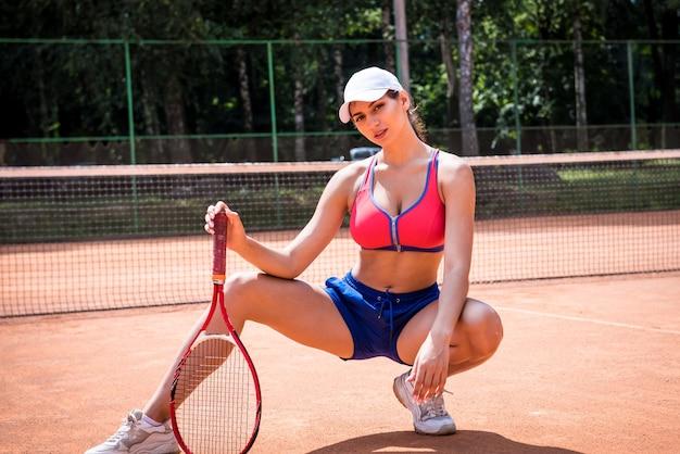テニスコートで若い運動女性の肖像画