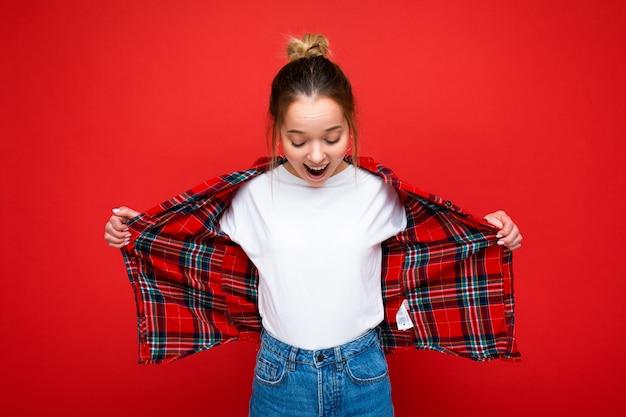 Портрет молодой привлекательной удивленной позитивной счастливой шокированной хипстерской блондинки в стильной красной рубашке