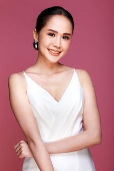 ピンクの背景に笑みを浮かべて白いウェディングドレスを着て若い魅力的なアジアの女性の肖像画。結婚式前の写真撮影のコンセプト。