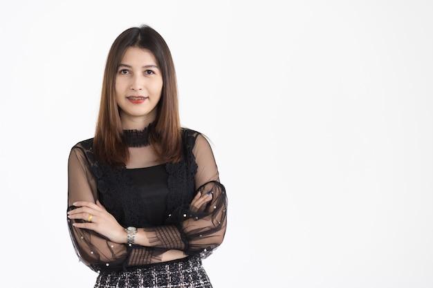 自信を持って笑っている黒い露出ドレスを身に着けている茶色の髪を持つ若い魅力的なアジアの女性の肖像画。孤立。