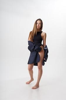 長い髪、黒いボディスーツの素足を持つ若い魅力的なアジアの女性の肖像画