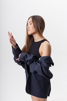 검은 bodysuit 및 흰색 스튜디오 배경에 고립 된 파란색 정장에 긴 머리를 가진 젊은 매력적인 아시아 여자의 초상화. cyclorama에 포즈를 취하는 마른 예쁜 여성. 아름다운 여인의 모델 테스트