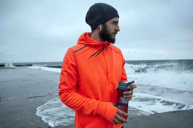寒い曇りの日に海辺に立っている間、彼のイヤホンで音楽を聴いているひげを持つ若い魅力的な運動モデルの肖像画。フィットネスとスポーツのコンセプト