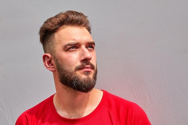 Портрет молодого привлекательного бородатого кавказца с серьезным взглядом в красной футболке на сером фоне.
