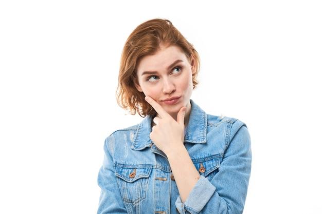 Портрет молодой привлекательной красивой вдумчивой студентки redhead думать смотря copyspace, изолированный на белой предпосылке. женщина в синих джинсах