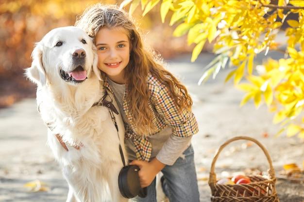 Портрет молодой привлекательной белокурой девушки с собакой. владелец домашнего животного. золотистый ретривер и его владелец осенью.