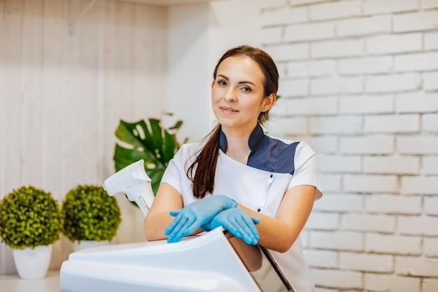 Портрет молодой привлекательной брюнетки-женщины-доктора в синих медицинских перчатках и униформе, позирующей с машиной для удаления волос в белом шкафу. скопируйте пространство.