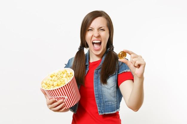흰색 배경에 격리된 팝콘과 비트코인 양동이를 들고 영화를 보고 비명을 지르며 캐주얼한 옷을 입은 젊은 갈색 머리 여성의 초상화. 영화 개념의 감정.