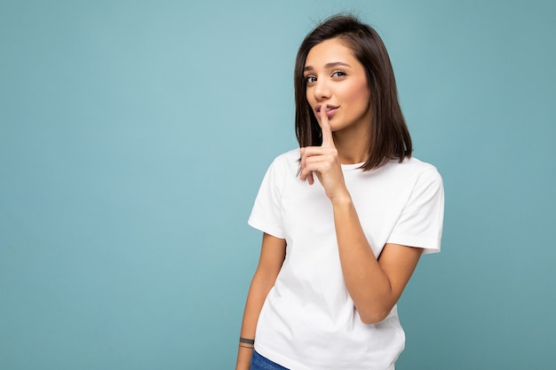 복사 공간이 파란색 배경에 고립 된 mockup에 대 한 캐주얼 흰색 티셔츠를 입고 성실한 감정을 가진 젊은 매력적인 갈색 머리 여자의 초상화는 침묵 남아 있습니다.