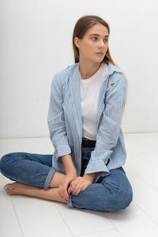 白い背景で隔離のtシャツとブルージーンズの長い茶色の髪を持つ若い魅力的な白人女性の肖像画。スタジオの床に座っている細いきれいな女性。美しい女性のモデルテスト