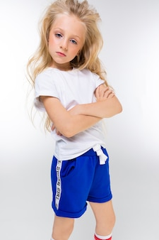 Портрет молодой привлекательной очаровательной блондинки в спортивной одежде стоит на белом фоне.