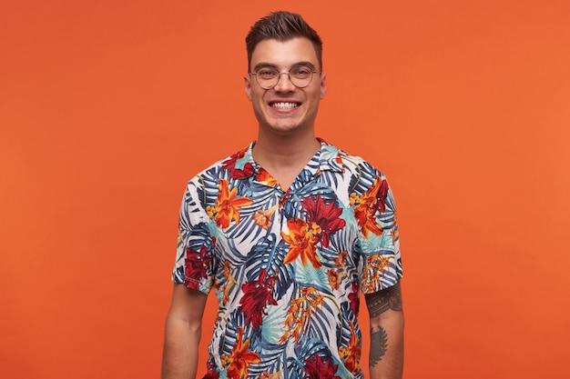 Портрет молодого привлекательного веселого парня в цветочной рубашке, выглядит счастливым, стоит на оранжевом фоне и широко улыбается.